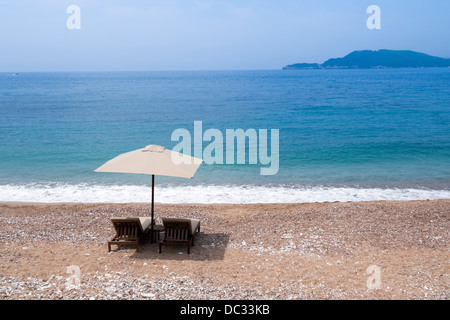 two sunbeds under sunshade on the empty sand beach - Stock Photo