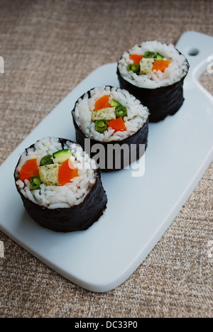 Vegetarian maki sushi rolls with rice, carrots, zucchini, green beans, tofu and nori seaweed in white dish on natural - Stock Photo