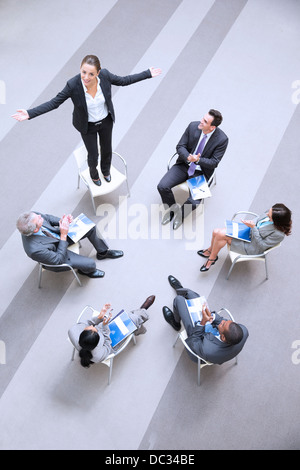 High angle view of businesswoman standing on chair in circle with co-workers - Stock Photo