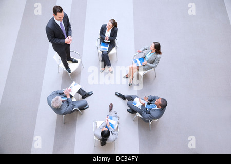 High angle view of businessman standing on chair in circle with co-workers - Stock Photo