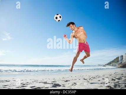 Man in swim trunks heading soccer ball on beach - Stock Photo