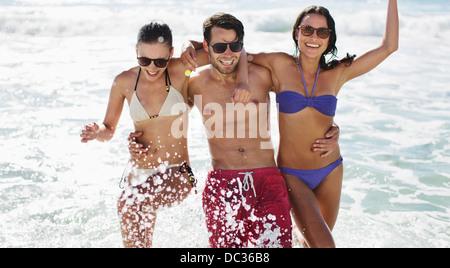 Portrait of enthusiastic friends splashing in ocean - Stock Photo