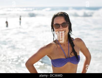 Portrait of smiling woman in bikini and sunglasses at beach - Stock Photo