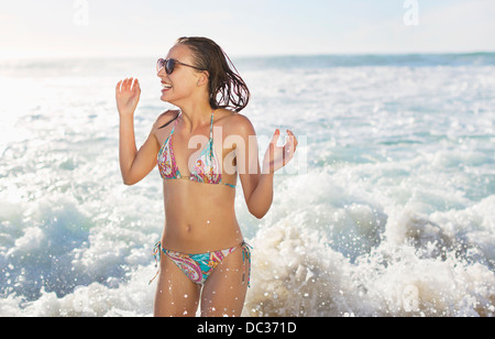 Happy woman in bikini splashing in ocean - Stock Photo