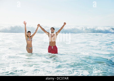 Portrait of enthusiastic couple holding hands with arms raised in ocean - Stock Photo