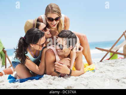 Happy friends laying on top of each other on beach - Stock Photo