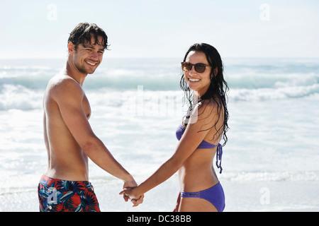Portrait of happy couple holding hands on beach - Stock Photo