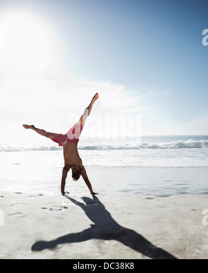 Man in swim trunks doing handstand on beach - Stock Photo