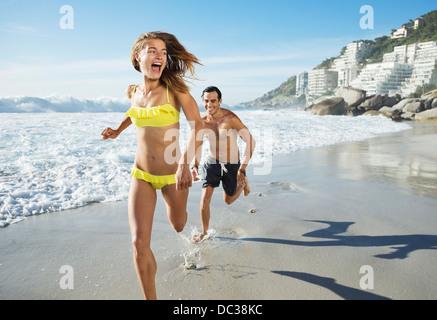 Man chasing happy woman on beach - Stock Photo