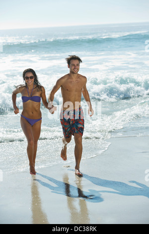 Happy couple holding hands and running on beach - Stock Photo