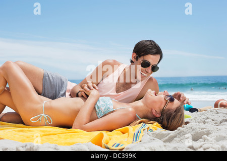 Happy couple laying on blanket at beach - Stock Photo