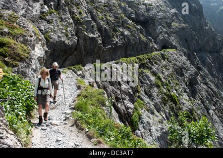 Wanderer auf Felsenweg in der Uinaschlucht - Hiker  on steep rock trail, Val d Uina - Stock Photo