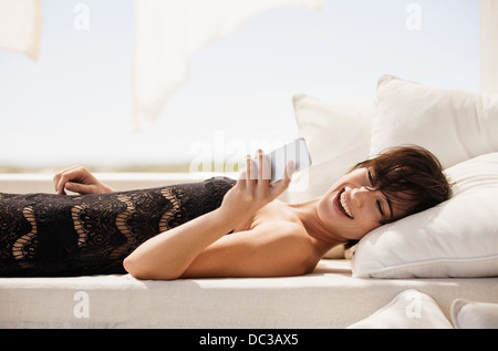 Smiling woman text messaging with cell phone on patio sofa - Stock Photo
