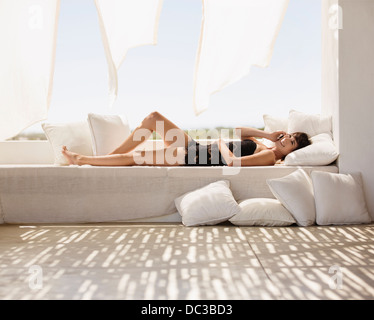 Smiling woman laying on patio sofa talking on cell phone - Stock Photo