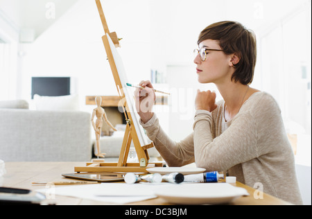 Woman painting on easel at table - Stock Photo
