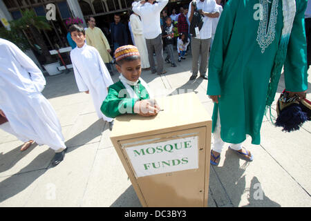 London, UK. 8th August 2013. A Muslim boy donates money during Eid at the Regent's Mosque in London which marks - Stock Photo