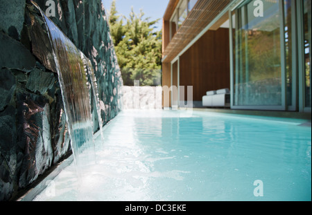 Waterfall emptying into pool of modern house - Stock Photo