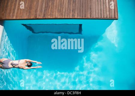 Woman in luxury swimming pool - Stock Photo