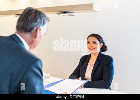 Recruiter (middle aged business man) checking the candidate, an attractive younger woman, during job interview - Stock Photo