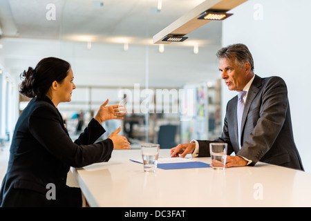 Recruiter (middle aged business man) checking the candidate, an attractive younger woman,during job interview with - Stock Photo