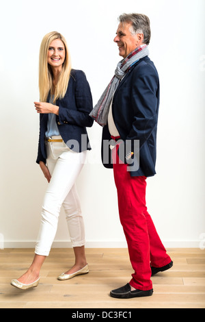 Portrait of a handsome mature man in casual modern clothes flirting with a much younger beautiful woman. - Stock Photo