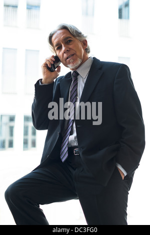 An elderly handsome business man at the office building on his mobile phone against bright background - Stock Photo