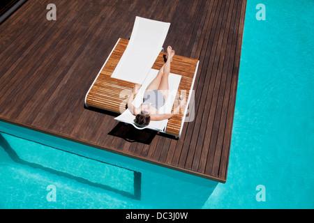 Woman sunbathing at poolside - Stock Photo