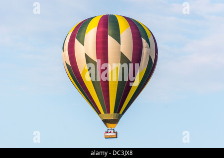 A hot air balloon with passengers, rising in the sky in calm conditions, above Amboise town, in the Indre-et-Loire - Stock Photo
