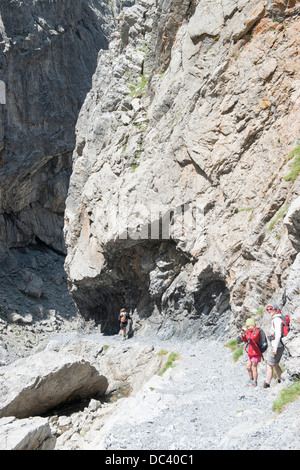Wanderer auf Felsenweg in der Uinaschlucht - Hiker on the steep rock trail, Val d Uina - Stock Photo