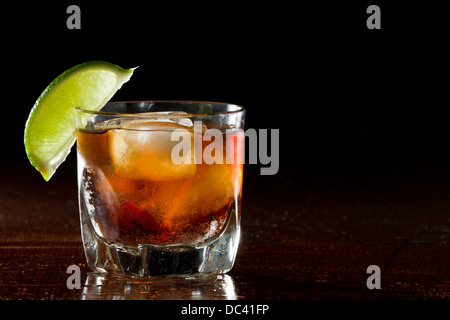 cuba libre, rum and cola cocktail served in a short glass with a lime garnish - Stock Photo
