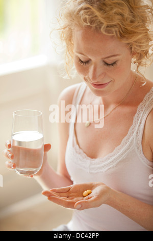 Woman holding glass of water and pills - Stock Photo