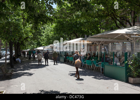 Street restaurant cafe on tree lined street in Barcelona - Stock Photo