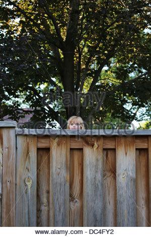 A little girl peeking over a tall fence. - Stock Photo