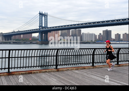 American woman runs under Manhattan Bridge - Stock Photo