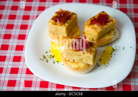 Spanish tapa: Spanish omelet with Iberian loin. - Stock Photo