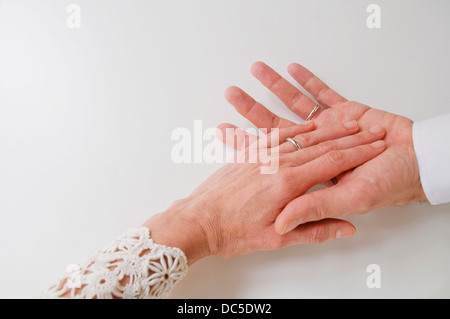 Mature couple's hands wearing wedding rings. - Stock Photo