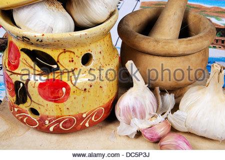Ceramic garlic pot, garlic bulbs and pestle and mortar on a wooden chopping board. - Stock Photo