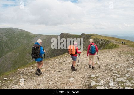 Hikers hiking from Carnedd Dafydd mountain top to Carnedd Llewelyn in Carneddau mountains of Snowdonia National - Stock Photo