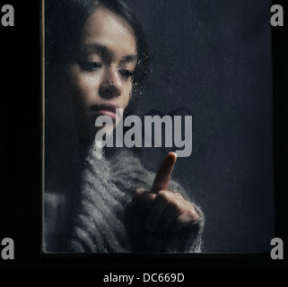 Beautiful girl drawing heart on wet window - Stock Photo