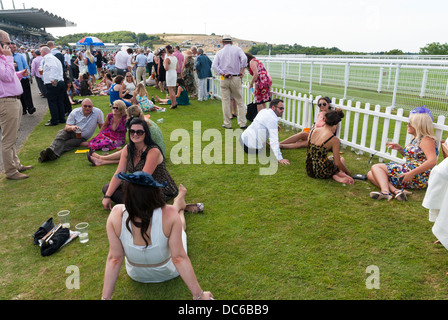 Ladies resting their feet by the rails on a horse race track - Stock Photo