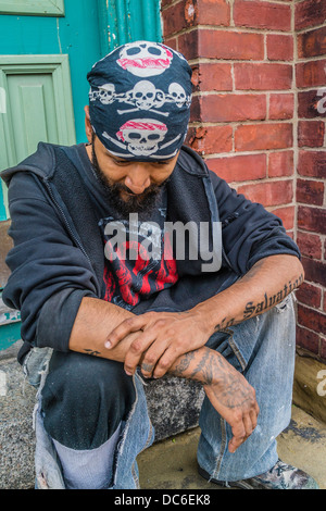 A Hispanic gang member sits on a front stoop of a house in St. John, Nova Scotia with tattooed arms and black headscarf. - Stock Photo