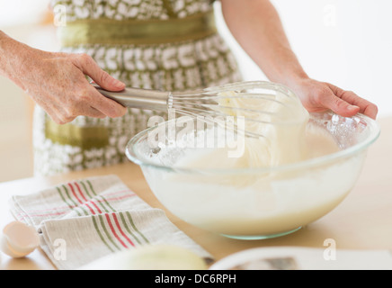 Midsection of woman whisking batter - Stock Photo