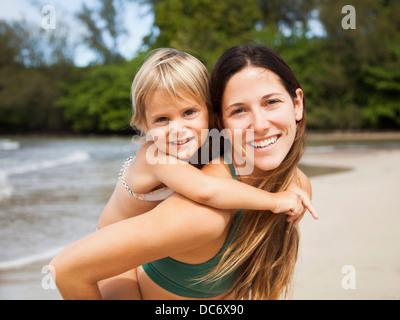 USA, Hawaii, Kauai, Mother with daughter (2-3) on beach - Stock Photo