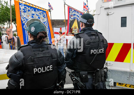 Belfast, Northern Ireland. 10th August 2013 - PSNI officesr wearing a soft baseball cap watch as loyalists protest - Stock Photo