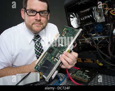 Man with computer and various hardware components - Stock Photo