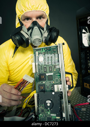 Man dealing with computer virus (figurative) or toxic chemicals heavy metals with computer and various hardware - Stock Photo