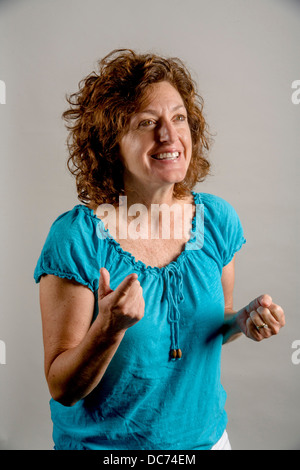 A 50 year old auburn haired woman demonstrates positive enthusiasm. - Stock Photo