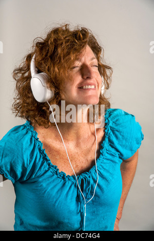 A 50 year old auburn haired woman enjoys music played on headphones. - Stock Photo
