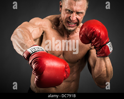 Heavyweight Boxer with red gloves punching - Stock Photo