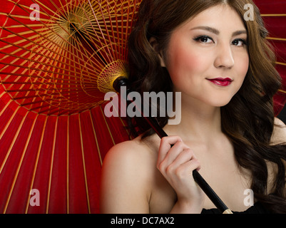 Beautiful young Japanese woman in her twenties with traditional red handmade Oil-paper umbrella WAGASA - Stock Photo